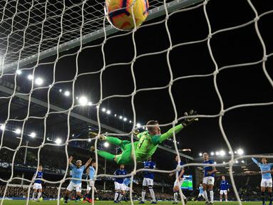 Kiper Everton, Jordan Pickford gagal menghalau bola tandukan bek Manchester City, Aymeric Laporte selama pertandingan lanjutan Liga Inggris di Goodison Park Stadium (6/2). City menang atas Everton 2-0. (Peter Byrne/PA via AP)