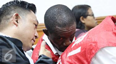 Terdakwa kasus narkotika sabu 6,3 kg Arinze Petrus Eneh berbincang dengan kuasa hukumnya saat mengikuti sidang vonis di PN Jakarta Barat, Rabu (11/5). Sidang dengan tuntutan hukuman mati ditunda hingga minggu depan. (Liputan6.com/Immanuel Antonius)