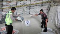 Petugas menunjukkan barang bukti beras oplosan yang diamankan penyidik di Pasar Induk Beras Cipinang, Jakarta, Jumat (7/10). Bareskrim Polri bongkar gudang mafia beras oplosan di Pasar Induk Beras Cipinang. (Liputan6.com/Yoppy Renato)