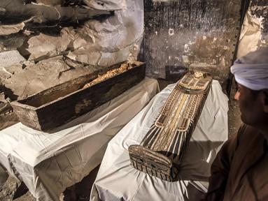Pekerja Mesir berdiri dekat mumi wanita bernama Thuya dalam sarkofagus yang baru dibuka di Kota Luxor, Sabtu (24/11). Mumi itu diawetkan dengan baik di dalam sarkofagus yang belum pernah dibuka sejak lebih dari 3.000 tahun lalu. (Khaled DESOUKI/AFP)