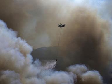 Sebuah helikopter berpartisipasi dalam operasi pemadaman kebakaran hutan di Koycegiz, Mugla, Turki, Senin (9/8/2021). Kebakaran hutan yang terjadi di tengah gelombang panas ganas telah berkobar selama berhari-hari di lebih dari setengah provinsi Turki. (AP Photo/Emre Tazegul)
