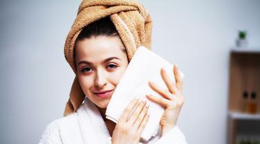 Gambar Ilustrasi Wanita Menepuk Wajahnya Dengan Handuk Setelah Mencuci Muka