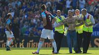 Petugas keamanan menangkap suporter yang trun ke dalam lapangan saat laga Leicester City melawan West Ham Unitd di King Power Stadium, Leicester, (5/5/2018).  West Ham menang 2-0. (AFP/Lindsey Parnaby)