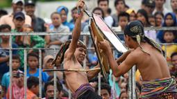 Dua pepadu (petarung) melakukan duel dalam kesenian tradisional peresean di Praya, Lombok Tengah, Selasa (19/2). Peresean merupakan festival adu ketangkasan dan kekuatan antara pemuda di kalangan suku Sasak Lombok. (MOH EL SASAKY/AFP)