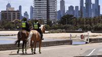 Polisi berpatroli dengan menunggang kuda di sepanjang St Kilda Esplanade di Melbourne (26/10/2020). Australia telah menghabiskan berbulan-bulan di bawah pembatasan yang berat setelah menjadi episentrum gelombang kedua negara itu. (AFP Photo/William West)