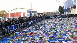 Pemain dan staf Leicester City (kiri) memberi penghormatan kepada korban kecelakaan helikopter yang menewaskan pemilik Leicester City Vichai Srivaddhanaprabha di luar Stadion King Power, Inggris, Senin (29/10). (Paul Ellis/AFP)