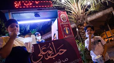 Anak laki-laki makan popcorn selama bulan suci Ramadan di Bilad al-Qadeem, ibukota Bahrain, Manama, di tengah pandemi COVID-19 yang sedang berlangsung (10/5/2020). (AFP/Mazen Mahdi)