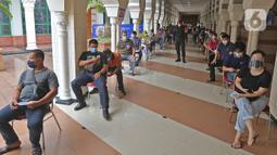 Pedagang saat antre untuk menjalani vaksinasi COVID-19 di Pasar Tanah Abang Blok A, Jakarta, Rabu (17/2/2021). Vaksinasi COVID-19 tahap kedua yang diberikan untuk pekerja publik dan lansia itu dimulai dari pedagang Pasar Tanah Abang di blok A, B, F, dan G. (Liputan6.com/Herman Zakharia)
