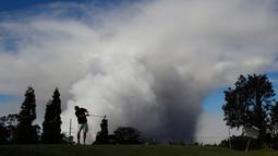 Mike Walls bermain golf saat kepulan asap abu vulkanik berembus dari puncak gunung Kiluaea di Volcano, Hawaii (21/5). Gunung Kilauea mulai meletus pada 3 Mei yang membuat sekitar 40 bangunan hangus terbakar. (AP Photo/Jae C. Hong)