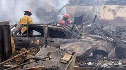 Petugas pemadam memeriksa lokasi kebakaran besar yang melanda permukiman Cantagallo di Lima, Peru, Jumat (4/11). Kebakaran mengakibatkan sekitar 300 rumah rata dengan tanah dan memaksa ribuan warganya mengungsi. (REUTERS/Guadalupe Pardo)