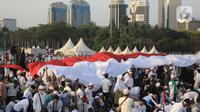 Massa membentangkan bendera Merah Putih saat mengikuti acara Munajat dan Maulid Akbar 2019 #ReuniMujahid212 di kawasan Monas, Jakarta, Senin (2/12/2019). Aksi dimulai dengan salat tahajud bersama pada pukul 03.00 WIB dan ditutup dengan doa yang berakhir pada 08.00 WIB. (Liputan6.com/Herman Zakharia)