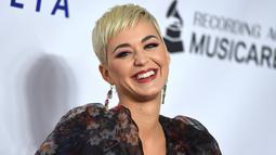 Penyanyi Katy Perry tersenyum saat berpose menghadiri pesta Gala Musicares Person of The Year 2019 di Los Angeles (8/2). Katy Perry tampil menawan mengenakan gaun hitam bermotif kembang dengan belahan hingga paha terbuka. (AP Photo/Jordan Strauss)