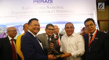 Gubernur Sumut Edy Rahmayadi (kedua kanan) menerima cenderamata dari Ketua Dewan Pembina DPN Perhimpunan Advokat Indonesia (Peradi) Otto Hasibuan (kedua kiri) ketika Rapat Kerja Nasional (Rakernas) Peradi di Medan, Kamis (6/12). (Liputan6.com/HO/Djoko)