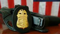 Lencana dan pistol FBI. Baru-baru ini FBI menerbitkan lebih dari 1500 dokumen berkaitan dengan investigasi mereka terkait penembakan di Sandy Hook Elementary School pada 2012. (Sumber Wikimedia Commons)