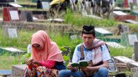 """Warga berdoa saat berziarah di TPU Karet Pasar Baru Barat, Jakarta, Sabtu (16/6). Ziarah kubur atau """"nyekar"""" pada hari raya lebaran merupakan salah satu tradisi umat muslim untuk mendoakan sanak keluarga yang meninggal dunia. (Liputan6.com/Arya Manggala)"""