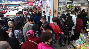 Warga mengantre untuk mendapatkan masker wajah gratis di luar sebuah toko kosmetik di Tsuen Wan, Hong Kong, Selasa (28/1/2020). Hong Kong terkonfirmasi memiliki delapan kasus infeksi virus corona. (AP Photo/Achmad Ibrahim)