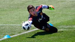 Kiper Kepa Arrizabalaga menepis bola saat mengikuti latihan tim Spanyol selama Piala Dunia 2018 di Krasnodar Academy  (21/6). Pemuda 23 tahun itu resmi menjadi kiper pemain termahal dunia setelah diboyong Chelsea. (AFP Photo/Pierre-Philippe Marcou)