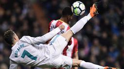 Striker Real Madrid, Cristiano Ronaldo, berebut bola dengan bek Girona, Jonas Ramalho, pada laga La Liga di Stadion Santiago Bernabeu, Senin (19/3/2018). Real Madrid menang 6-3 atas Girona. (AFP/Javier Soriano)