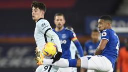 Bek Everton, Mason Holgate (kanan), berebut bola dengan gelandang Chelsea, Kai Havertz, dalam laga lanjutan Liga Inggris 2020/21 pekan ke-12 di Goodison Park Stadium, Sabtu (12/12/2020). Everton menang 1-0 atas Chelsea. (AFP/Peter Powell/Pool)