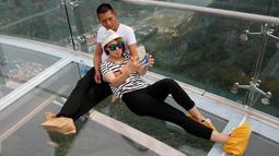 Pasangan berfoto selfie di atas platform kaca di Jurang Shilin, Beijing, Cina, (27/5). Para pengunjung diwajibkan mengenakan alas kaki khusus untuk mencegah kerusakan kaca saat berwisata ketempat ini. (REUTERS/Kim Kyung-Hoon)