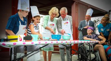 Pangeran Charles bersama sang istri Camilla Parker membuat kue lamington bersama anak-anak di Brisbane, Australia, Rabu (4/4). Kegiatan itu dilakukan dalam kunjungannya ke Rumah Sakit Anak Lady Cilento. (Patrick HAMILTON/POOL/AFP)