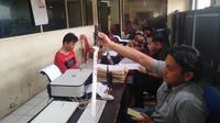 Eko Saputra, tersangka penganiayaan pedagang di Pasar Tradisional 16 Ilir Palembang, saat diinterogasi di Polresta Palembang (Liputan6.com / Nefri Inge)