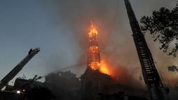 Petugas pemadam kebakaran memadamkan gereja La Asuncion setelah diserang dan dibakar saat puluhan ribu orang berunjuk rasa di Kota Santiago, Chile, Minggu (18/10/2020). Demonstrasi itu digelar untuk memperingati satu tahun protes besar menuntut kesetaraan di Chile. (AP Photo/Esteban Felix)