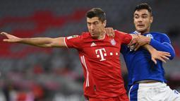 Penyerang Bayern Munchen, Robert Lewandowski, berebut bola dengan bek Schalke, Ozan Kabak, pada laga Liga Jerman di Allianz Arena, Sabtu (19/9/2020) dini hari WIB. Bayern Munchen menang 8-0 atas Schalke. (AFP/Christof Stache)