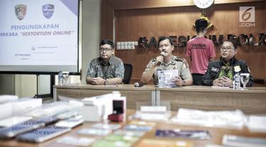 Kasubag Opinev Bag Penum Humas Polri AKBP Zahwani Pandra Arsyad (tengah) saat rilis kasus tindak pidana pemerasan secara online dengan cara penyediaan jasa video call sex (vcs) di Bareskrim Polri, Jakarta, Jumat (15/2). (Liputan6.com/Faizal Fanani)