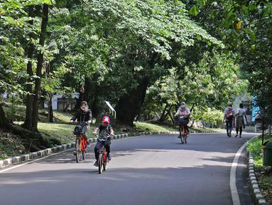 Pengunjung bersepeda di Kebun Raya Bogor, Jawa Barat, Selasa (7/7/2020). Kebun Raya Bogor menerapkan pemesanan tiket secara daring serta kapasitas pengunjung dibatasi hanya 50 persen. (Liputan6.com/Herman Zakharia)