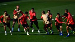 Para pemain Real Madrid melakukan pemanasan selama berlatih jelang menghadapi FC Viktoria Plzen pada lanjutan grup G Liga Champions di Valdebebas, Spanyol (22/10). Saat ini Madrid berada di posisi kedua dengan nilai tiga. (AFP Photo/Gabriel Bouys)