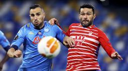 Striker Granada, Jorge Molina (kanan) berebut bola dengan bek Napoli, Nikola Maksimovic dalam laga leg kedua babak 32 Besar Liga Europa 2020/21 di Diego Armando Maradona Stadium, Kamis (25/2/2021). Granada kalah 1-2 dari Napoli. (LaPresse via AP/Alessandro Garofalo)