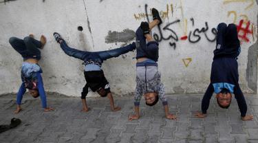 Anak laki-laki Palestina melakukan pemanasan saat mengikuti pelatihan tari di kamp pengungsi Al-Nusairat, Jalur Gaza tengah (5/11/2019). Pada 2012, Ahmed dan teman-temannya mendirikan sekolah tari di kamp pengungsi Nuseirat. (AP Photo/Hatem Moussa)