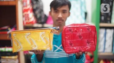 Pekerja memperlihatkan hasil dari sampah plastik yang diproduksi di kawasan Pasar Minggu, Jakarta, Senin (13/1/2020). Rumah daur ulang plastik itu memproduksi barang dari limbah plastik seperti tas, payung, dompet dan koper dengan harga jual Rp20ribu hingga Rp700ribu (Liputan6.com/Immanuel Antonius)