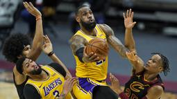 Pebasket LA Lakers, LeBron James (tengah) berusaha memasukkan bola dalam laga lanjutan babak reguler NBA melawan Cleveland Cavaliers di Quicken Loans Arena, Selasa (26/1/2021). (Foto: AP Photo/Tony Dejak)