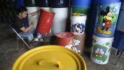 Faiz (21) melukis tong sampah dengan gambar tokoh kartun di Setu, Tangerang Selatan, Banten, Kamis (1/10/2020). Faiz mengecat ulang tong bekas dan melukisnya dengan tokoh-tokoh kartun, lalu menjualnya dengan harga Rp 85 hingga 120 ribu per unit. (merdeka.com/Dwi Narwoko)