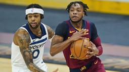 Pebasket Cleveland Cavaliers, Darius Garland, berusaha melewati pebasket Minnesota Timberwolves, D'Angelo Russell, pada laga NBA di Rocket Mortgage FieldHouse, Senin (1/2/2021). Cavaliers menang dengan skor 100-98. (AP/Tony Dejak)
