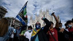 Para pendukung dan fans Inter Milan mengibarkan bendera dan meneriakkan yel-yel di kawasan Piazza Duomo, Milan, Minggu (2/5/2021) merayakan kepastian Inter Milan merebut gelar juara Scudetto Liga Italia 2020/2021. (AFP/Piero Cruciati)