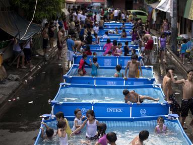 Anak-anak bermain di kolam portabel yang diberikan oleh pemerintah setempat untuk mendinginkan tubuh pada saat musim panas di Manila, Filipina (12/4). (AFP Photo/Noel Celis)