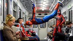 Penari underground yang mengenakan kostum Spiderman tampil di kereta bawah tanah Saint Petersburg, Rusia pada 21 Mei 2021. Penari berkostum Spiderman tersebut tampil berjungkir, melompat dan melakukan gerakan akrobatik di kabin kereta bawah tanah. (Olga MALTSEVA / AFP)