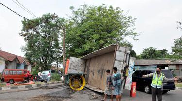 Jumat (15/8/14), sebuah truk yang membawa mesin untuk kapal, terbalik di dekat stasiun Cakung, Jakarta. (Liputan6.com/Panji Diksana)