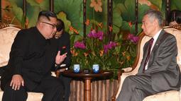 Pemimpin Korea Utara, Kim Jong-un berbincang dengan Perdana Menteri Singapura Lee Hsien Loong di Istana Kepresidenan Singapura, Minggu (10/6). Kim Jong-un dan Donald Trump akan bertemu 12 Juni. (AFP Photo/HO/Kementerian Kominfo Singapura)