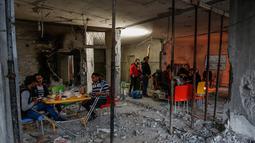 Orang-orang Palestina yang diamputasi berbuka puasa di sebuah pusat komunitas yang dihancurkan selama eskalasi dua hari, di Rafah, Jalur Gaza selatan (8/5/2019). Para pemimpin Palestina di Gaza setuju untuk gencatan senjata dengan Israel pada 6 Mei 2019. (AFP Photo/Said Khatib)