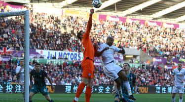 Kiper Southampton, Alex McCarthy menghalau bola dari kejaran pemain Swansea, Andre Ayew pada lanjutan Premier League di Liberty Stadium, Swansea, (8/5/2018). Swasea City kalah dari Soton 0-1. (AFP/Geoff Caddick)