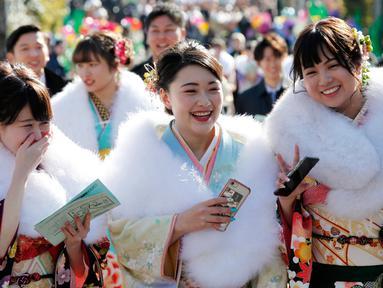 Tiga wanita berpakaian Kimono saat menghadiri upacara perayaan Coming of Age Day atau Hari Kedewasaan di Tokyo, Jepang  (14/1). Hari Kedewasaan jatuh di hari Senin minggu kedua di bulan Januari. (AP Photo/Koji Sasahara)