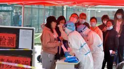 Petugas medis mengambil sampel warga saat yang lainnya antre untuk tes COVID-19 di dekat daerah perumahan di Qingdao, China, Senin (12/10/2020). Lebih dari 9 juta orang yang tinggal di kota Qingdao, menjalani tes virus Corona (COVID-19) secara massal setelah muncul kasus baru. (Chinatopix via AP)