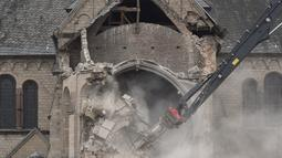 Sejumlah awak media melihat petugas dibantu alat berat membongkar Gereja St. Lambertus di Desa Immerath, Jerman (8/1). Pembongkaran dilakukan untuk perluasan pertambangan batubara, penghasil energi listrik. (AFP Photo/Henning Kaiser)