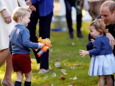 Pangeran George dan Putri Charlotte terlihat bergembira saat bermain pistol gelembung sabun dalam sebuah pesta untuk anak-anak di Government House di Victoria, British Columbia, Kanada, (29/9). (REUTERS/Chris Wattie)