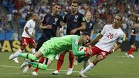 Kiper Kroasia, Danijel Subasic mengamankan bola dari kejaran pemain Denmark, Yussuf Yurary Poulsen pada laga 16 besar Piala Dunia 2018 di Nizhny Novgorod Stadium, Rusia, (1/7/2018). Kroasia menang 3-2 lewat adu penalti. (AP/Darko Bandic)