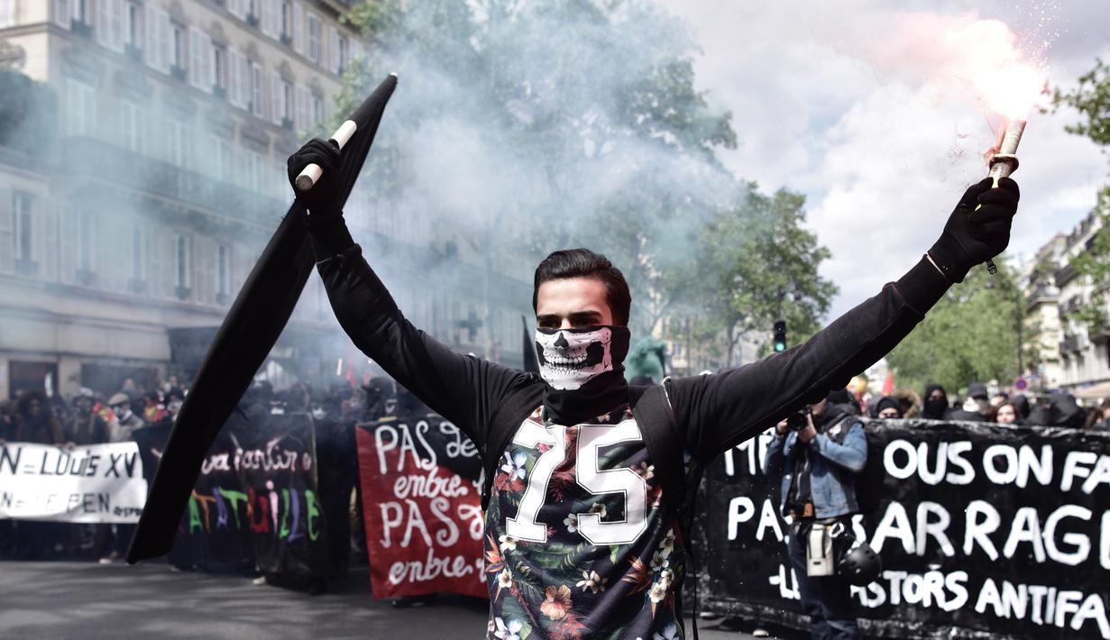 Seorang pria memegang bendera sambil manyalakan suar asap saat demonstrasi perayaan May Day di Paris, Prancis,Senin (1/5). Hari Buruh Internasional atau May Day di Paris, diwarnai bentrokan antara pengunjuk rasa dengan polisi.  (PHILIPPE LOPEZ/AFP)